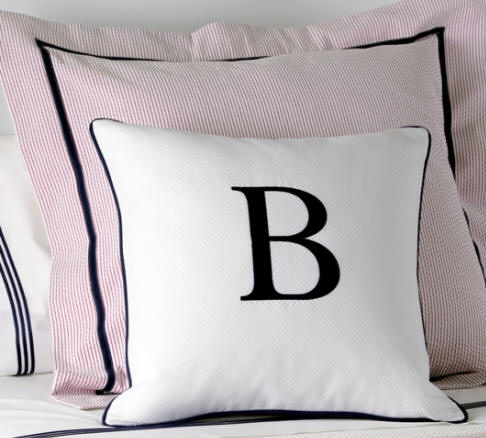 Monogrammed single letter pillow on white diamond pique and finished with a matching border.